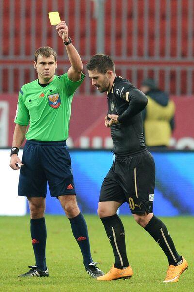 Судья показывает желтую карточку форварду ФК Рубин Марко Ливайя (справа)