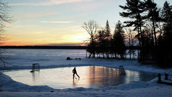 Юный спортсмен играет в хоккей на рассвете в Онтарио