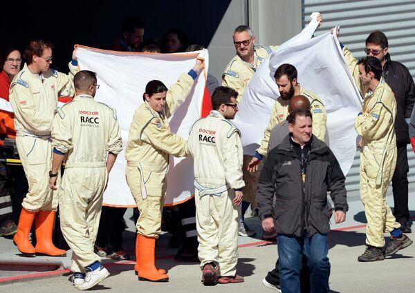 Медицинский персонал помогает эвакуировать попавшего в аварию пилота Макларен Фернандо Алонсо