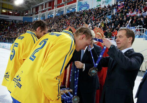 Председатель правительства России Дмитрий Медведев (справа) вручает серебряные медали бендистам сборной Швеции