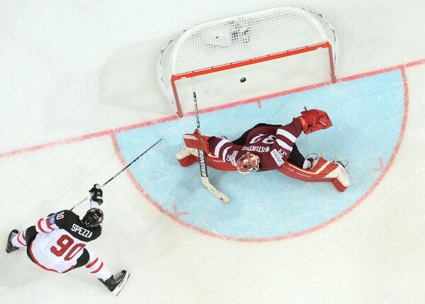 Форвард сборной Канады Джейсон Спецца (слева) забивает шайбу