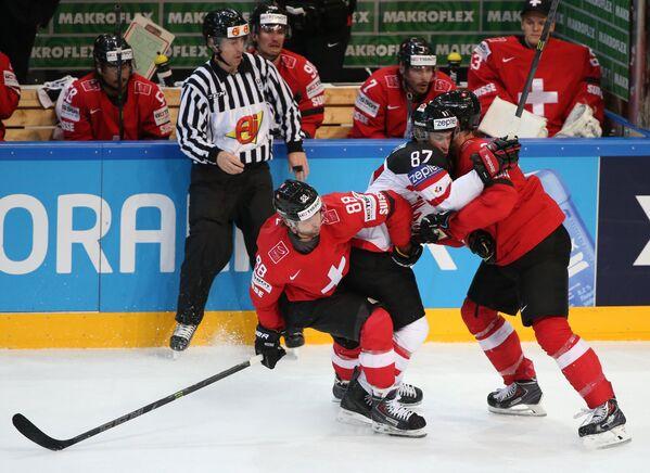 Нападающие сборной Швейцарии Кевин Роми, сборной Канады Сидни Кросби и защитник сборной Швейцарии Тимо Хельблинг (слева направо)