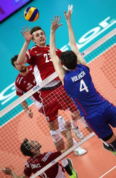 Блокирующий сборной Польши Матеуш Бенек (в центре) и блокирующий сборной России Артем Вольвич (справа)