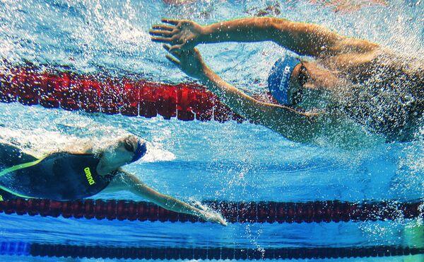 Спортсменки на дистанции во время соревнований по плаванию