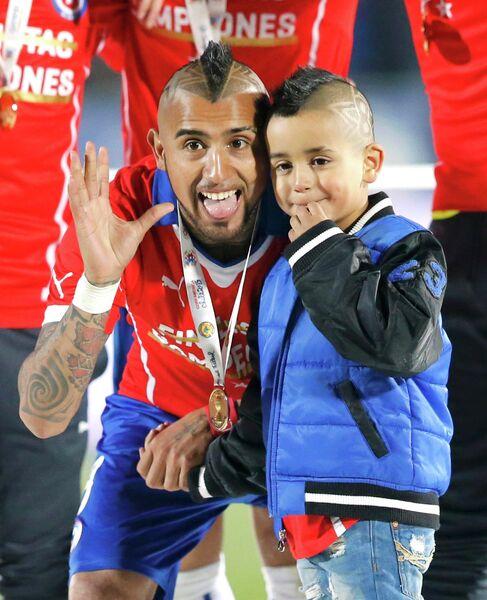 Полузащитник сборной Чили Артуро Видаль со своим сыном Алонсо после победы на Кубке Америки