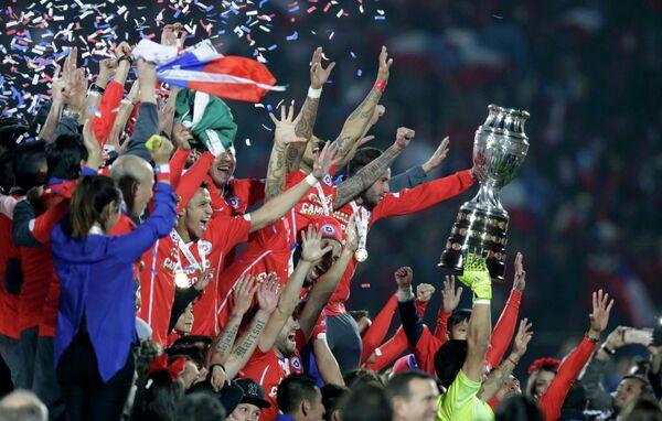 Футболисты сборной Чили с трофеем за победу на Кубке Америки