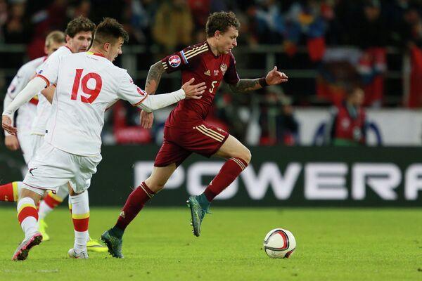 Нападающий сборной Черногории Стефан Мугоша и полузащитник сборной России Павел Мамаев (слева направо на первом плане)