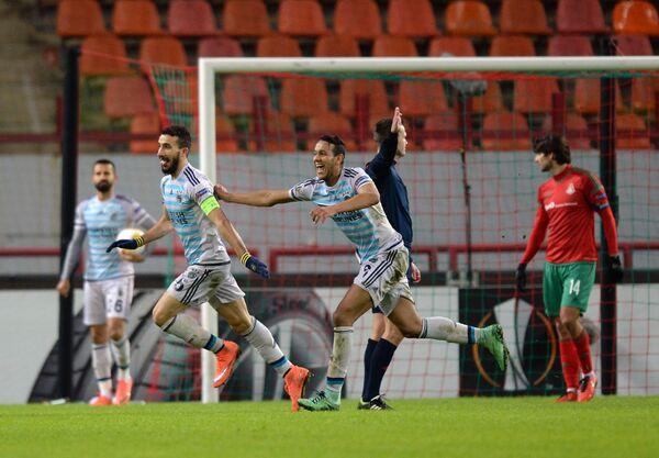 Футболисты Фенербахче Мехмет Топал (слева на первом плане) и Жосеф Соуза радуются забитому мячу