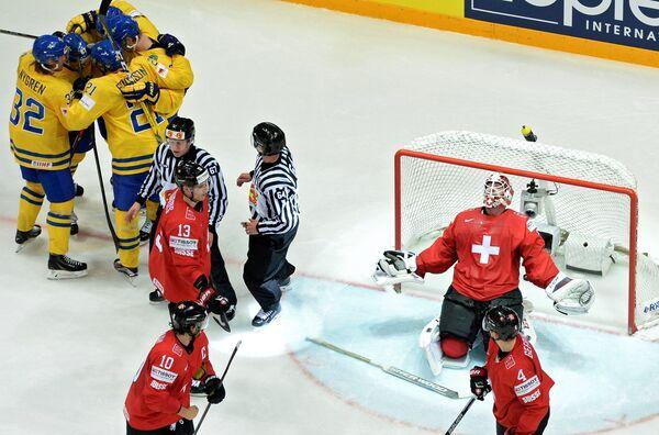 Вратарь сборной Швейцарии Рето Берра пропускает шайбу в свои ворота от шведских хоккеистов