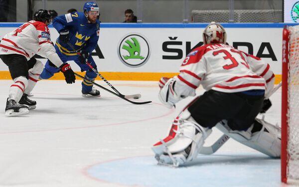 Защитник сборной Канады Мэтт Дамба, форвард сборной Швеции Линус Умарк и вратарь сборной Канады Кэм Тальбо (слева направо)