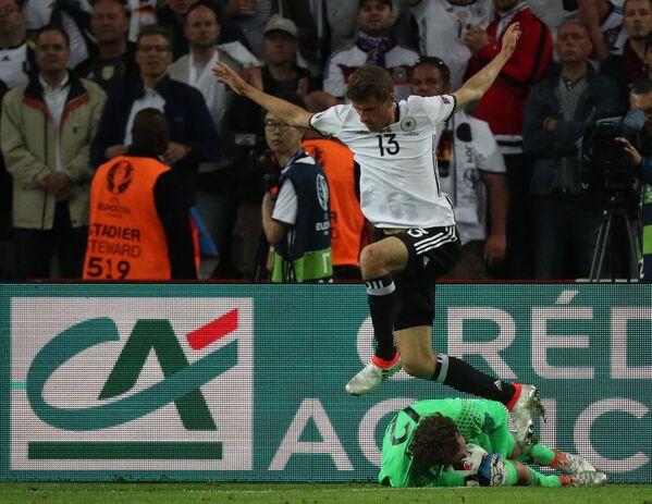 Форвард сборной Германии Томас Мюллер (вверху) и вратарь сборной Украины Андрей Пятов