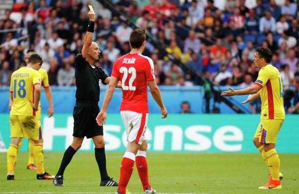 Главный арбитр встречи Сергей Карасев показывает желтую карточку нападающему сборной Румынии Клаудиу Кесеру