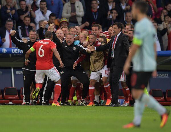Футболисты и тренерский штаб сборной Уэльса радуются забитому голу
